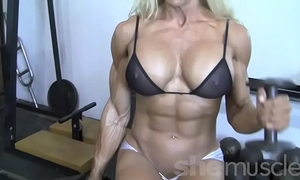 Sexy blond female bodybuilder in watch throughout top works out