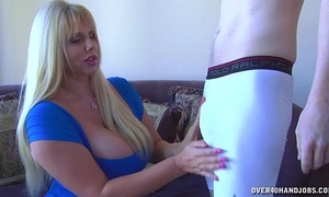 Huge-titted blond strokes a youthful guy's knob