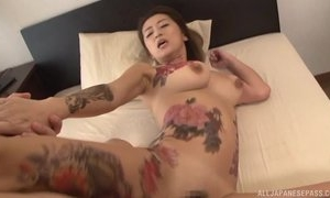 Tattooed Japanese MILF with big naturals gets fucked hard in threesome